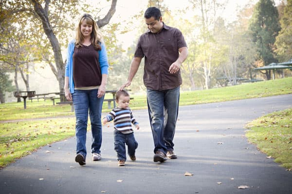 Pregnant woman walking with toddler and husband during sunset